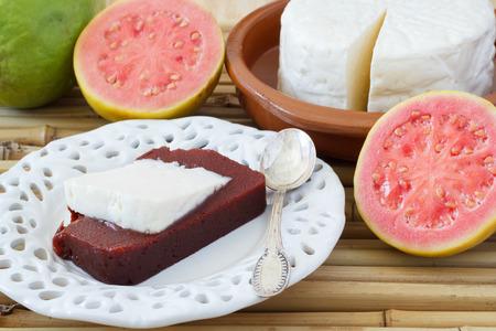 romeo and juliet: Brazilian dessert Romeo and Juliet on white plate, goiabada and Minas cheese with fresh goiaba on bamboo. Selective focus Stock Photo