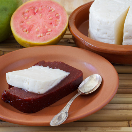 romeo and juliet: Brazilian dessert Romeo and Juliet, goiabada and Minas cheese with fresh goiaba on wooden table. Selective focus Stock Photo