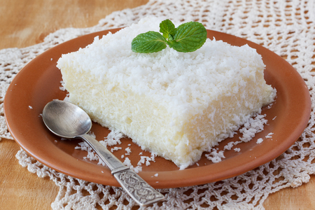 a dessert: Brazilian traditional dessert: sweet couscous (tapioca) pudding (cuscuz doce) with coconut on plate with spoon on wooden table. Selective focus