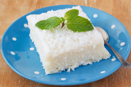 Brazilian traditional dessert: sweet couscous (tapioca) pudding (cuscuz doce) with coconut and mint on blue plate with spoon on wooden table. Selective focus