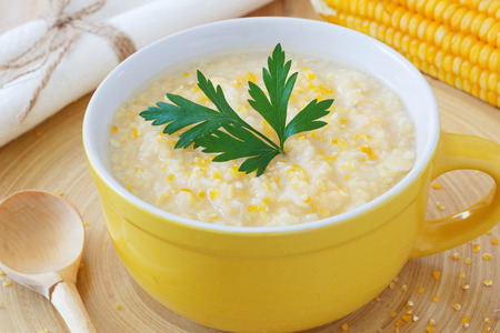 Brazilian corn soup canjiquinha in yellow bowl with fresh corn. Selective focus