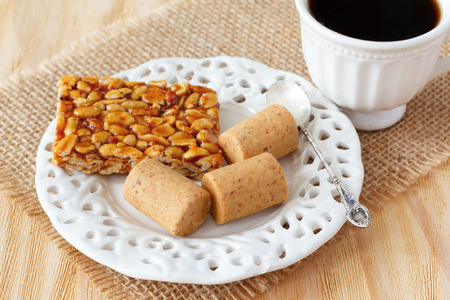 gozinaki: Pacoca - brazilian candy of ground peanut  and gozinaki on white vintage plate with cup of coffee. Selective focus