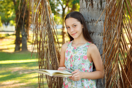 palm reading: Cute smiling teen girl reading book and looking to camera near palm tree, green grass in park. Selective focus