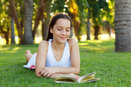Cute smiling teen girl reading book laying on green grass in park. Selective focus