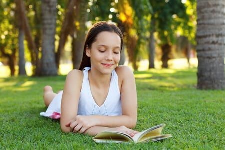 ni�as peque�as: Lindo libro muchacha adolescente sonriente lectura que pone en hierba verde en el parque. Enfoque selectivo Foto de archivo