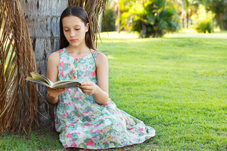 palm reading: Cute teen girl reading book sitting on green grass in park near palm tree. Selective focus. Copy space
