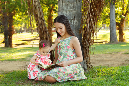 palm reading: Cute sisters teen and baby girl reading book on green grass near palm tree in park. Selective focus