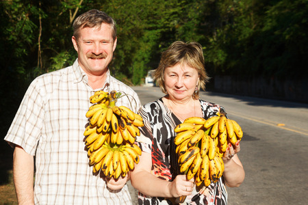 butch: Couple Man and woman smiling and holding butch of bananas near road. Selective focus