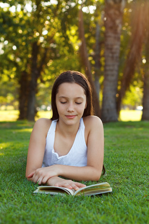 cute girl smiling: Cute teen girl reading book laying on green grass in park. Selective focus Stock Photo