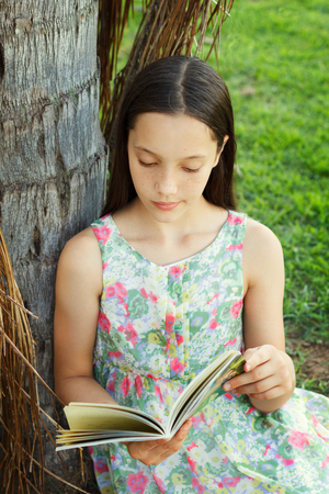 Cute teen girl reading book sitting on green grass near palm tree in park. Selective focus