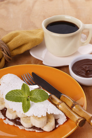 extracted: Casabe (bammy, beiju, bob, biju) - flatbread of cassava (tapioca) with banana and chocolate spread on orange plate with cup of coffee. Selective focus