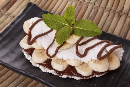 Casabe (bammy, beiju, bob, biju) - flatbread of cassava (tapioca) with banana and chocolate spread on black plate. Selective focus 免版税图像