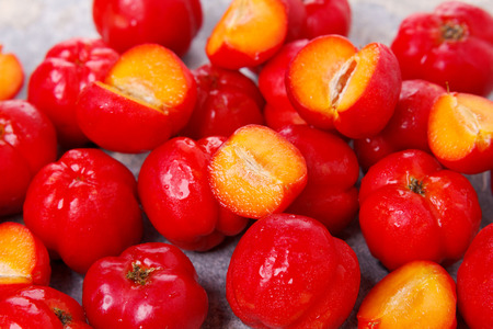 Closeup of Malpighia glabra (red acerola), tropical fruit in bowl on gray background. Selective focus. 免版税图像 - 49257154