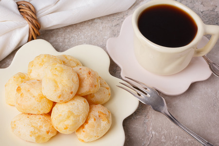 pao: Brazilian snack pao de queijo (cheese bread) on white plate with  cup of coffee on marble table. Selective focus