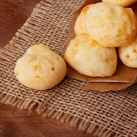 pao: Brazilian snack cheese bread (pao de queijo) in paper cone on wooden table. Selective focus Stock Photo