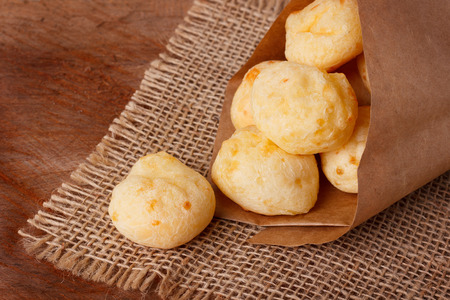Brazilian snack cheese bread (pao de queijo) in paper cone on wooden table. Selective focus 免版税图像