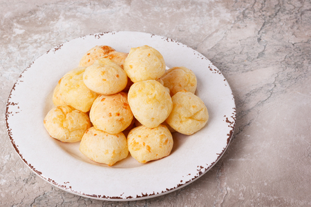 Brazilian snack cheese bread (pao de queijo) on plate on marble table. Selective focus
