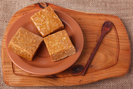 Pacoca - brazilian candy of ground peanut on brown plate on wooden background. Selective focus