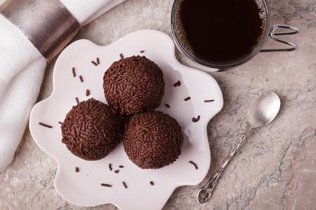 cafe bombon: trufas de chocolate bombón Brigadeiro brasileña en la placa con la taza de café en la mesa de mármol. enfoque selectivo Foto de archivo