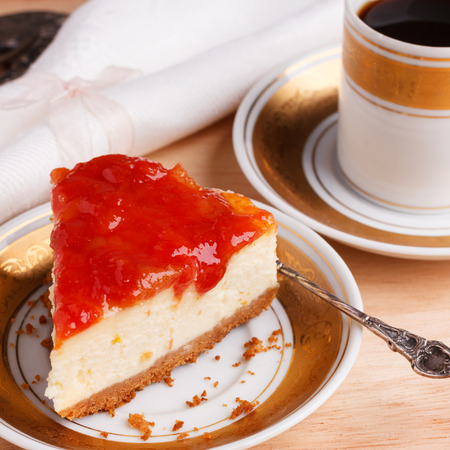 Cheesecake with brazilian goiabada jam of guava on white gold vintage plate with coffee. Selective focus Stock Photo
