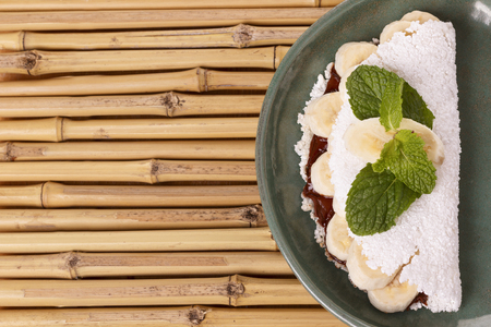 Casabe (bammy, beiju, bob, biju) - flatbread of cassava (tapioca) with banana and chocolate spread on green plate on bamboo. Selective focus Imagens