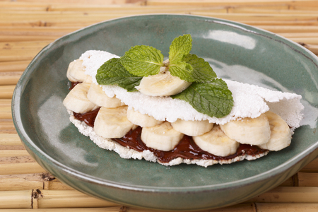 Casabe (bammy, beiju, bob, biju) - flatbread of cassava (tapioca) with banana and chocolate spread on green plate on bamboo. Selective focus 免版税图像