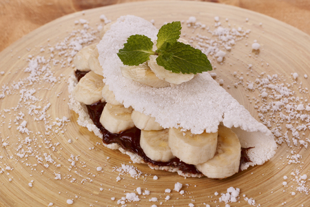 extracted: Casabe (bammy, beiju, bob, biju) - flatbread of cassava (tapioca) with banana and chocolate spread on wooden table. Selective focus