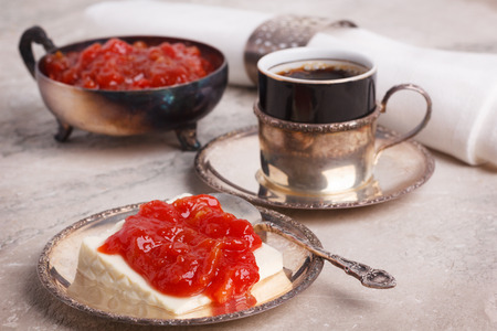 Brazilian dessert Romeo and Juliet, goiabada jam of guava and cheese Minas with vintage silver cup of coffee on marble table. Selective focus
