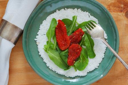 Casabe (bammy, beiju, bob, biju) - flatbread made from cassava (tapioca) with sun-dried tomatoes and  rucola (arugula) on green plate. Selective focus