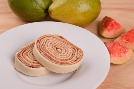 Bolo de rolo (swiss roll, roll cake) Brazilian dessert on white plate on wooden table. Selective focus 免版税图像