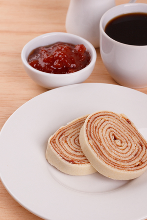 Swiss roll (cake) with red berry jam and cup of coffee on wooden table. Selective focus. Copy space 免版税图像