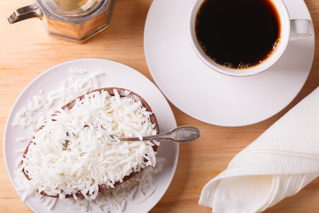 Chocolate egg with filling of coconut for Easter and cup of coffee on wooden background. Selective focus 免版税图像