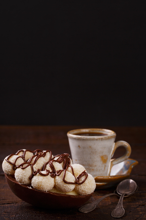 Chocolate egg with filling for Easter and cup of coffee on wooden background. Selective focus