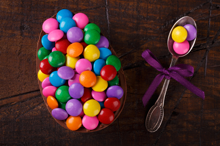 Chocolate egg with filling of colorful candy for Easter on wooden background. Selective focus