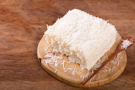 Brazilian traditional dessert: sweet couscous (tapioca) pudding (cuscuz doce) with coconut on wooden board. Selective focus