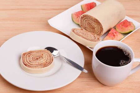 Bolo de rolo (swiss roll, roll cake) Brazilian dessert with cup of coffee on wooden table. Selective focus 免版税图像