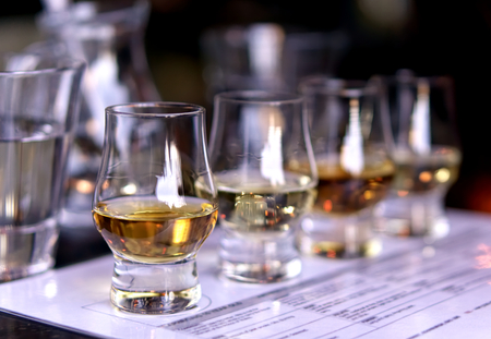 Close-up / selective focus a flight of whiskies. Four different whiskies in whisky tasting glasses. 스톡 콘텐츠