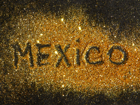 glister: Blurry inscription Mexico on golden glitter sparkle on black background