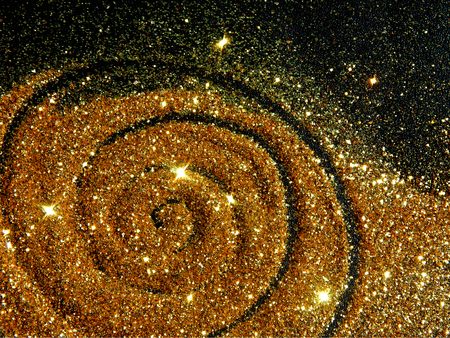 glister: Blurry golden spiral of glitter sparkle on black background like a star galaxy