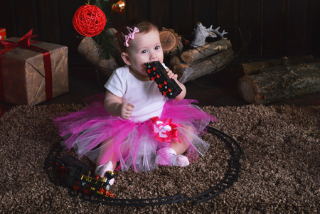 Cute little girl sitting under the Christmas tree. Baby holding a toy train in her hands Stock Photo