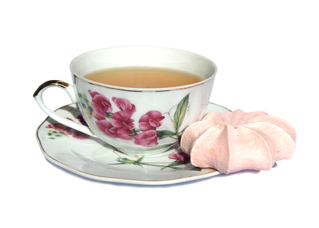 Pink meringue cake, white cup of green tea and saucer with a picture of pink flowers on white background