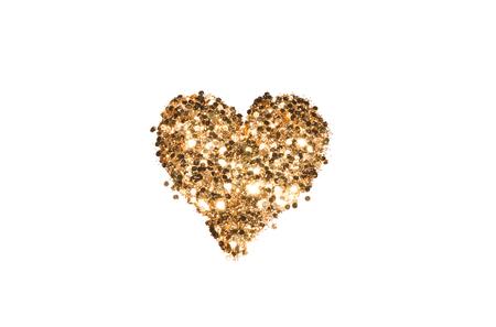 Abstract heart of golden glitter sparkles on white background.