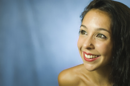 Face of beautiful young woman on blue background