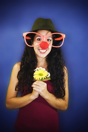 Young girl smiling clown on blue background Stock Photo