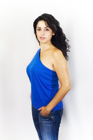 Portrait of a young woman with blue shirt, jeans and white background