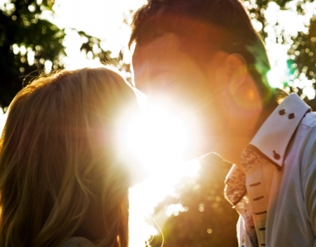 Portrait of an attractive couple sharing a passionate kiss backlit