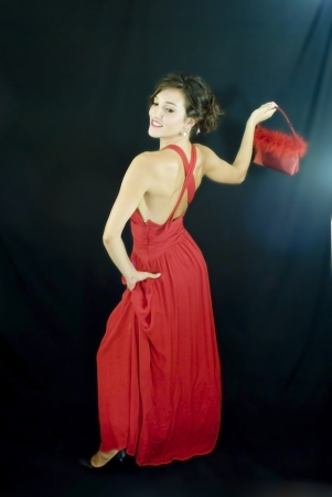 Beautiful woman with red dress on black background Banco de Imagens