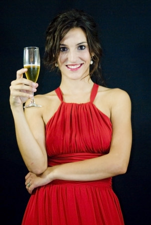 Beautiful woman with red dress and glass of champagne on black background Banco de Imagens