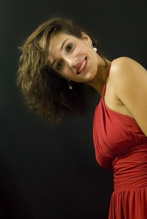 Mulher bonita com vestido vermelho no fundo preto