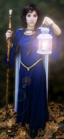Retrato de uma mulher bonita medieval com vela e vara